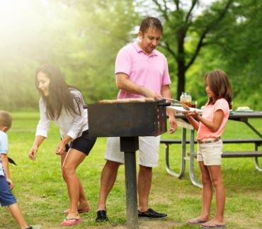 Family grilling together at a park